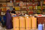 Grocery store worker in djellaba with female customer in purple Hijab in Fes el Bali Medina Morocco