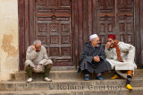 Two Moroccan men talking laughing one sitting apart at the steps to the north entrance of Andalusian Mosque