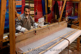 Weaver setting up a horizontal wooden hand loom in a cloth shop Fes Morocco