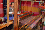Fast moving weaver operating a horizontal wooden hand loom in a cloth shop Fes el Bali Morocco