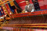 Weaver operating a horizontal wooden hand loom in a cloth shop Fes el Bali Morocco