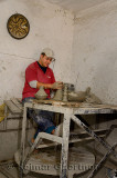 Worker throwing clay tagine pots on a turning wheel in a Fes el Bali Medina shop Morocco