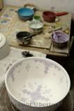 Hand painting glaze patterns on a bowl in a ceramic shop Fes el Bali Medina Morocco