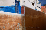 Young woman looking down from a red ochre wall in the blue city of Oudaia Kasbah Rabat Morocco