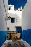 Young men moving a refrigerator through a small blue door in the narrow alley of Oudaia Kasbah Rabat Morocco