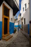 Young girl running along a narrow blue alley of Oudaia Kasbah Rabat Morocco