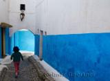 Young girl running along a blue alley of Oudaia Kasbah Rabat Morocco