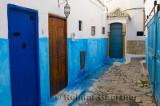 Brown door among blue doors in an alley of Oudaia Kasbah Rabat Morocco