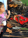 Young girl listening to presenter at table with old tools