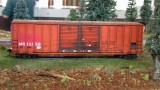 Rusty boxcar in the grass.