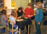 Teacher and her young  pupils learning how to mold clay