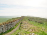 Hadrian's  Wall,partially  reconstructed, heads east into the mist.