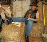 leather rancher sitting hay bales.jpg
