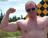 beefy biker hunk flexing arms highway.JPG