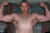 older hairy bodybuilder flexing arms.jpeg