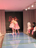 young customers of the Barbie flagship store in Shanghai walk the store's runway.