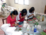Young girls painting designs on ceramic ashtrays.