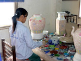 Vietnamese girl putting the glaze on these unfired ceramic pieces.