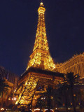 Close-up of the Eiffel Tower illuminated at night.