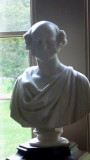 A marble statue of Martin Van Buren in front of the window in the Library.