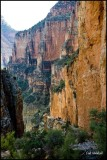 Hikers dwarfed by canyon wall.