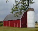 dark red barn with bright white silo...
