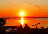 couple avec vélo devant le coucher de soleil