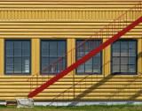 escalier rouge et maison jaune