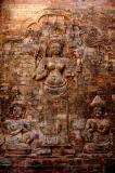 four-armed Lakshmi, Vishnu's consort, holding her attributes.  Attendants kneel in prayer at the feet of the goddess