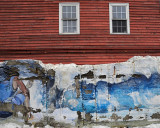 The sad decay of a wall mural and the windows overlooking it