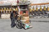 Bicycle rickshaw in front of prayer wheels of the Potola kora circuit