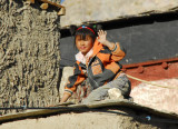A young girl waves from her rooftop perch