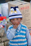 Tibetan boy with a cute hat but dirty face