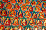 Thousands of small Buddha images painted on the cloister walls around the central courtyard of the Kelsang Temple Complex