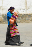 Tibetan woman carrying a bundled up child