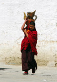 Monk carrying a heavy jug
