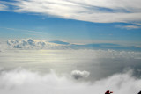 The Big Island of Hawaii reaching up out of the clouds in the distance
