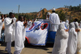The wedding car is covered with a decorated white cloth