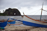 Outrigger fishing boat pulled up on the beach with Bantay Abot Cave in the background