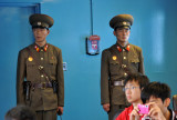 A pair of North Korean soldiers on ROK territory make sure no one leaves through the wrong door