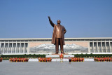 A lone woman bows in front of the statue of Kim Il Sung