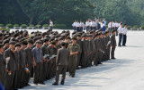 A large North Korean work unit dressed in Mao-suits arrives at the Mansu Grand Monument