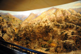 The diorama depicts the bravery of truck drivers delivering ammunition to the front under fire from U.S. Imperialist aircraft