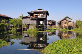Stilt house reflected in the mirror smooth later of Inle Lake