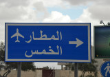 Libyan road sign for Tripoli Airport and Al Khoms, the modern city next to the ruins of Leptis Magna