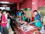 Part of the fish market houses a line of fish cleaners