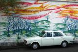 Iranian car parked in front of a mural in central Tehran