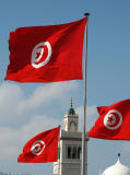 Tunisian flags with the minaret of the Kasbah Mosque