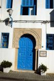 Typical Tunisian blue door on white house