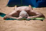 Man on beach sunbathing